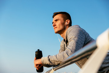 Attractive sportsman standing on quay, with bottle of water Wall mural