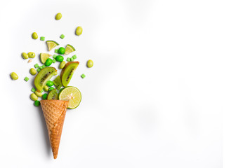 Ice cream cone flat lay image with green candy and kiwifruit packing into the cone.