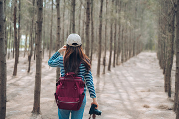 Woman photographer walking in the forest with backpack for take a photo and travel lifestyle relaxation on autumn and summer weekend.