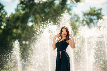 A girl is walking around the city, near a large fountain.