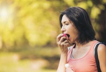 Older woman is eating apple after exercising to take care of their health.Eat healthy eating concept.