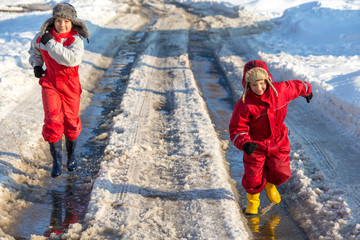 Two kids in rainboots running on the ice puddle