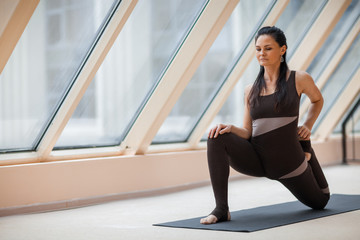 brunette woman in a dark jumpsuit standing in Horse rider exercise, anjaneyasana pose in front of large windows. working out, full length, wearing sportswea.