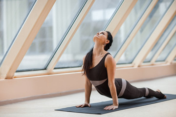 brunette woman practicing yoga concept, stretching in Cobra exercise, Bhujangasana pose in front of large windows. working out, full length, in front of large windows.