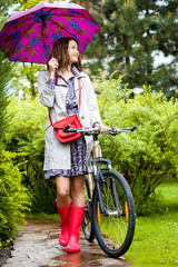 beautiful middle aged woman with umbrella and bicycle