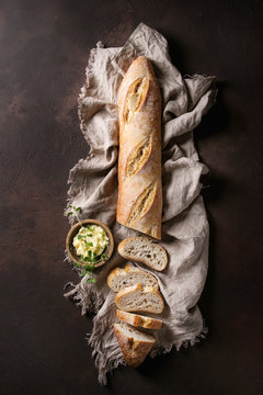 Loaf of sliced fresh baked artisan baguette bread on linen cloth with butter and herbsover dark brown texture background. Top view, copy space.