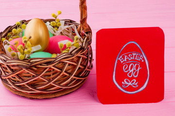 Wicker basket with Easter eggs. Red paper card with picture of Easter egg. Easter symbols and traditions.