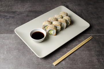 Roll with eel and sesame on a gray background