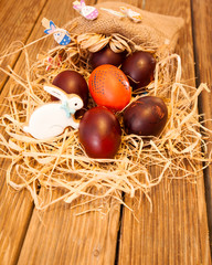 Chocolate Easter eggs over white rustic wooden background.