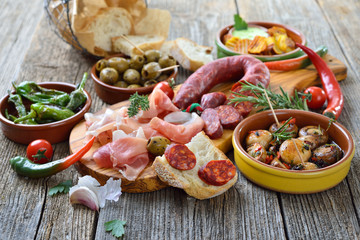 Photo sur Toile Buffet, Bar Iberische Spezialitäten: Spanische Chorizo, Serrano-Schinken und weitere Tapas – Typical Iberian bar food: Spicy chorizo sausage, Serrano ham and other mixed tapas