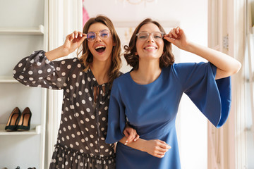 Two pretty young women shopaholics wearing glasses. Wall mural