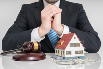 House auction concept. Lawyer with gavel and house model.