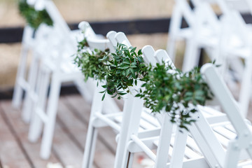 White chairs decorated with greenery and eucalyptus are in the zone of the wedding ceremony on the pier. Close-up decor