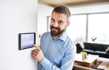 A man pointing to a tablet with smart home screen. Fotoväggar