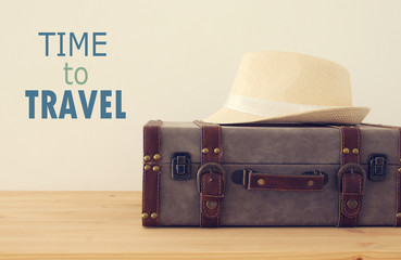 traveler vintage luggage, camera and fedora hat over wooden table. holiday and vacation concept.