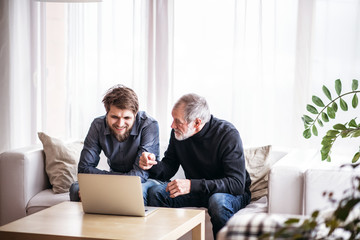 Hipster son and his senior father with laptop at home.