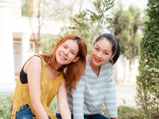 Two girls best friends sitting and relax in public park in the city.