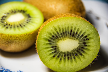 Kiwi cut in half and whole on a plate