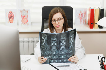 Female doctor sitting at desk with computer, film x-ray the brain by radiographic image ct scan mri in light office in hospital. Woman in medical gown in consulting room. Healthcare, medicine concept.