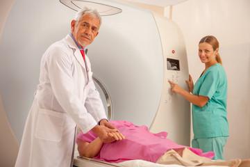 Elderly woman undergoing MRI scan under doctors supervision