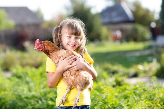 Child girl with hen in hands in rural