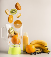 flying ingredients for making smoothies from oranges, kiwi and bananas, vegetarian healthy food, fruit lined around a green blender, space for text