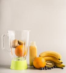 ingredients for making smoothies from oranges, kiwi and bananas, vegetarian healthy food, fruits lined around a green blender, space for text