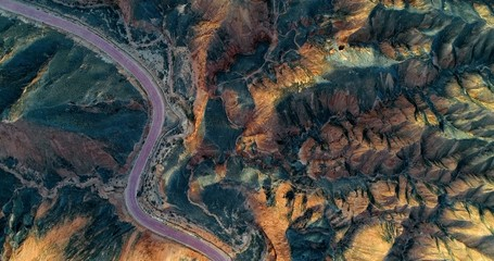 Aerial view on orange sandstone hills covered with sparse vegetation with curved, empty road creating a minimalistic landscape. Zhangye Danxia National Geopark, China. Wall mural