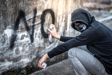 Mystery man in hoody jacket spraying word no on the wall in abandoned building. Anti social youth gangster problem concept. social disorder violence abuse foster system