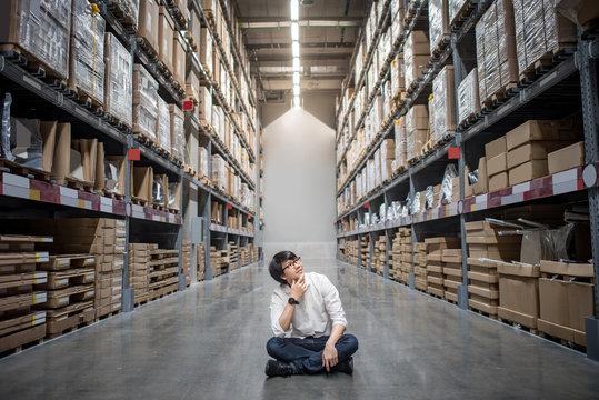 Young Asian man sitting between paper box shelves in warehouse choosing what to buy, shopping warehousing concept