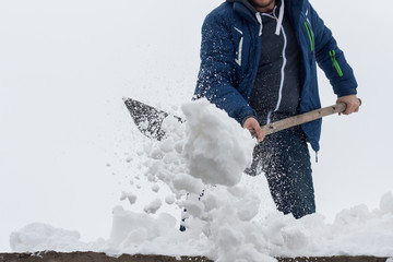 Young man clean a roof from snow by shovel. Spring snow removing after blizzard. Gray sky with copyspace.