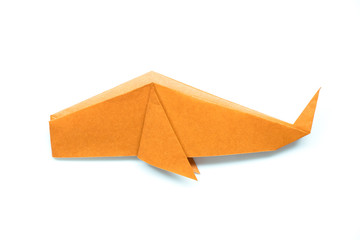 Orange origami paper in fish or whale shape on white background