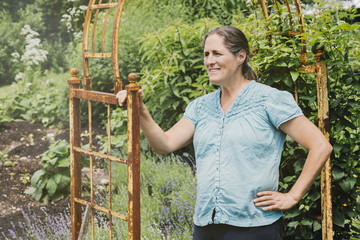 Smiling mature woman looking away while standing in garden