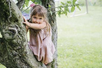 Portrait of cute playful girl sitting on tree against grassy field at park Fotoväggar