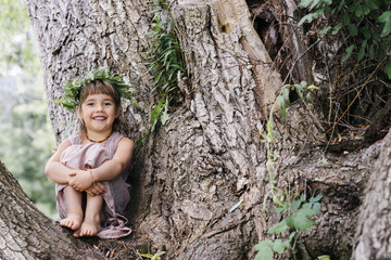 Portrait of girl wearing a leaf crown while sitting on tree branch