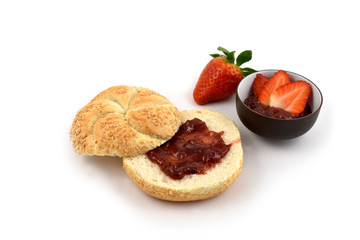 Bun with strawberry jam stock images. Strawberry with jam on a white background. Marmalade in a bowl. Breakfast still life. Pastry with marmalade