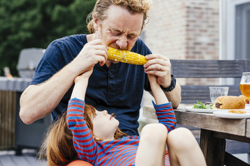 Father sitting with son eating corn on the cob