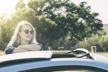 Smiling woman in sunglasses standing by car against trees at farm during sunny day