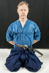 Caucasian male training Iaido, japanese sword sport. Hands behind his back. Sitting position.