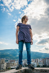 Woman standing on ancient wall with the city of Skopje in the background. Low angle position.
