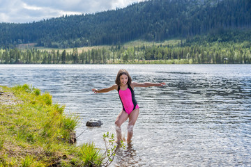Cute little brown haired girl in swimsuit spashing water in a mountain lake.