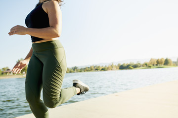 Young woman jogging by lake against clear sky