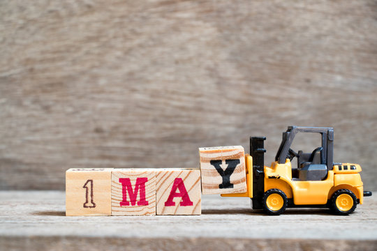 Toy forklift hold block Y to complete word 1may on wood background (Concept for calendar date 1 for month May)