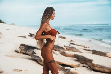 Sexy tattoed girl with tanned skin walking along the beach. Beautiful young blond woman with long hair in a red swimsuit resting by the ocean. A tourist with a beautiful figure on vacation