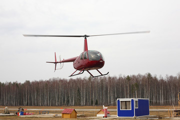 Aircraft - Red small helicopter makes flight at low height