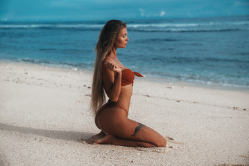 Amazing sexy girl with tattoo on her leg and attractive booty rests on the beach removes a bra from the body. Beautiful woman with tanned skin in a red bikini sits on the sand near the ocean