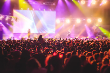 A crowded concert hall with scene stage lights, rock show performance, with people silhouette