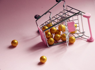 Shopping cart. Fallen Supermarket trolley full of golden balls on pink background. Consumerism concept photo.