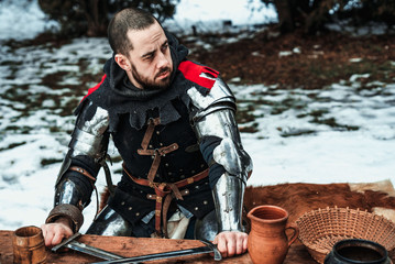 male knight sits at a wooden table