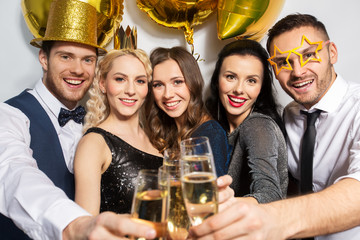 celebration, luxury and holidays concept - happy friends with golden party props clinking champagne glasses